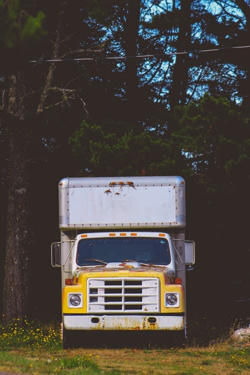 Moving truck among the trees.