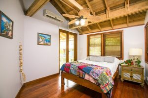 Beautiful bungalow-style bedroom on the sea, wooden floor, wooden ceiling fan