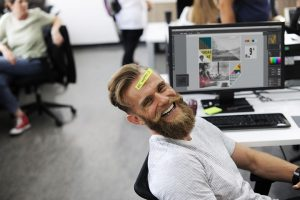 Man in front of a computer smiling and has a yellow post it on his forehead